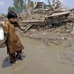 A young flood survivor walks in search of clean water before the rubble of houses destroyed by heavy floods in Nowshera near Peshawar.