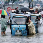 flood effected people pushing their rickshaws to safe locations in flood stricken villages.