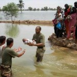 Rescue workers & Pakistan Army Soldiers helping people reach safe area.